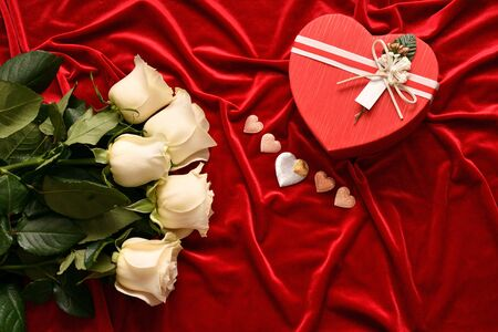 White roses and valentine's day gift on a red background Standard-Bild - 137775357
