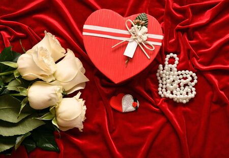 White roses and valentine's day gift on a red background Standard-Bild - 137775051