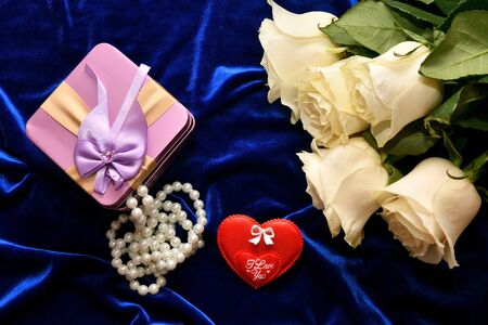 White roses and valentine's day gift on a blue background Standard-Bild - 138041822