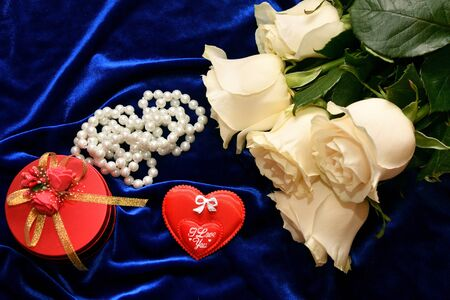 White roses and valentine's day gift on a blue background Standard-Bild - 137800066