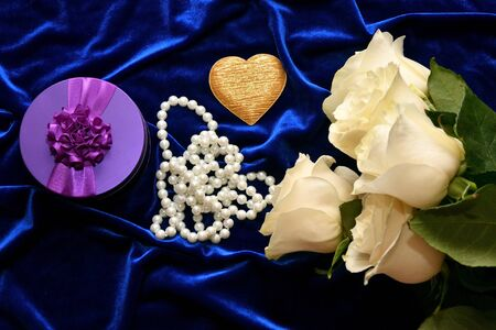 White roses and valentine's day gift on a blue background Standard-Bild - 137800376