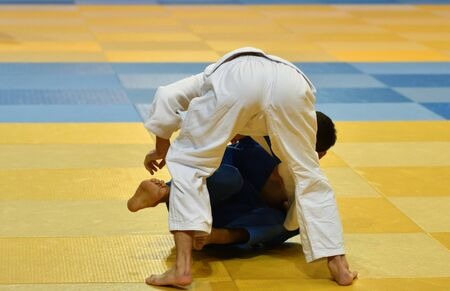 Two Boys judoka in kimono compete on the tatami Standard-Bild - 138573091