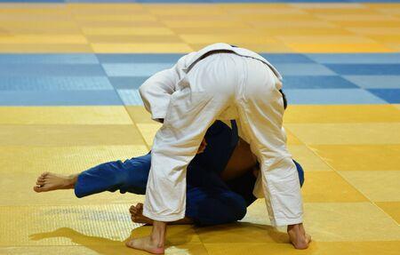 Two Boys judoka in kimono compete on the tatami Standard-Bild - 138573105