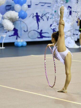 Girl performs mandatory exercises in rhythmic gymnastics