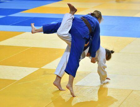 Two Girls judoka in kimono compete on the tatami Stock Photo