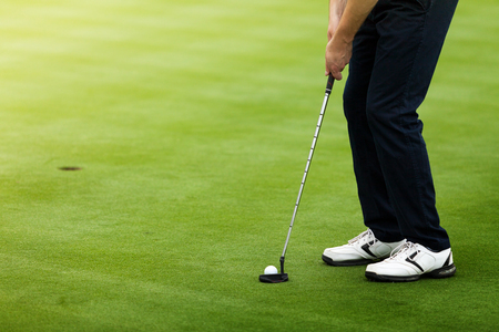 Golfer preparing for a putt on the green during golf course. Stock Photo