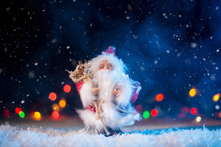 xmass: Santa Claus with presents standing on the wooden desk, blurred colorful lights in the background. Christmas concept. Stock Photo