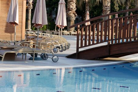 Folded sun loungers by the pool with a wooden bridge.