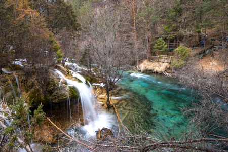 defrost: Waterfall in the mountains. The defrost water runs over the rocks. Water flowing over rocks and moss and trees. Water flowing waterfall on a river Stock Photo