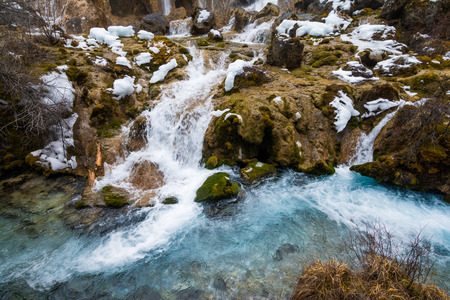 defrost: Waterfall in the mountains. The defrost water runs over the rocks. Water flowing over rocks and moss Stock Photo