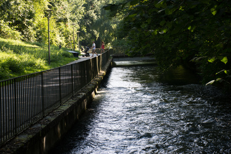 walking paths: River embankment in the park. The river in the park at walking paths in the shade. Fast water, trees and bridge Stock Photo