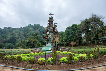 Man looks after the greenery on the field. The structure of the metal in the middle of the field with green plants. The structure of old metal spare parts for scaring birds.Sri Lanka, Dambulla