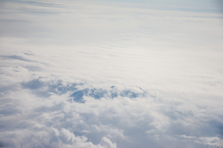 View of the mountains covered with snow from the airplane. Mountains in the clouds.