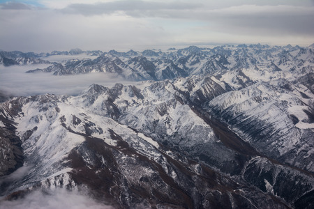 View of the mountains covered with snow from the airplane. Mountains to horizon. Mountain range in cloudy weather