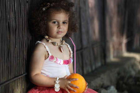 curly girl holding a tropical drink in her hands