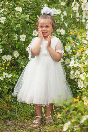 A little girl in a white dress of the bride in nature.