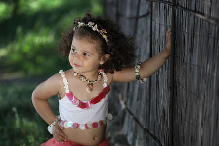 curly girl in a pink dress with shell decorations on the nature Фото со стока