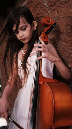 beautiful girl in a pink dress stands with a cello