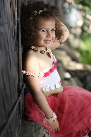 curly girl in a pink dress with shell decorations sits on the nature
