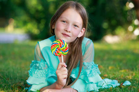 beautiful girl with colorful lollipop in the park