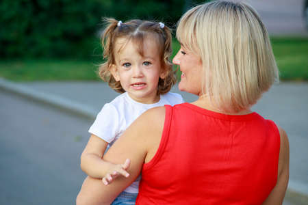 beautiful blonde mom in a red t-shirt with her daughter. group portrait