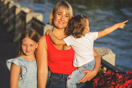 beautiful blonde mom in a red t-shirt with her daughters on the embankment. group portrait Фото со стока