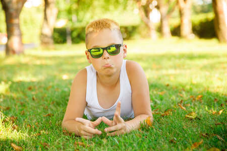 a blond boy in a white T-shirt with sunglasses lies on the grass in the park