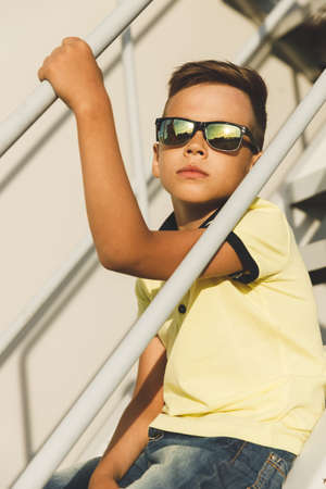 handsome asian boy in sunglasses on the stairs in a yellow t-shirt and jeans