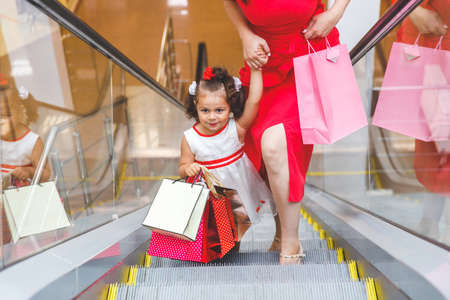 mom and daughter on the escalator in the mall with colored bags Archivio Fotografico