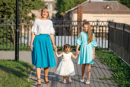 mom with daughters walks in the park in summer. family walk Фото со стока
