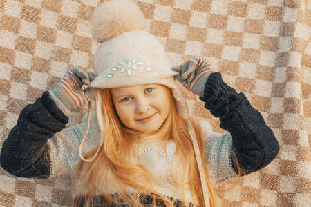 little blonde girl in a woolen hat in a plaid in the park
