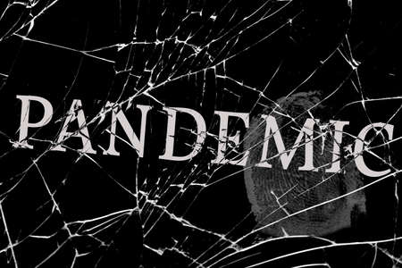 gloomy broken glass with cracks with the inscription pandemic