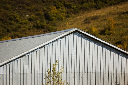 Building with gray corrugated roof and walls by autumn photo