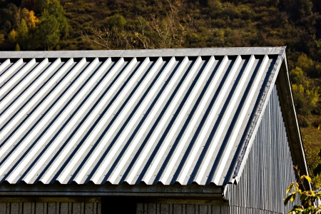 corrugated iron: The gray corrugated roof of a building