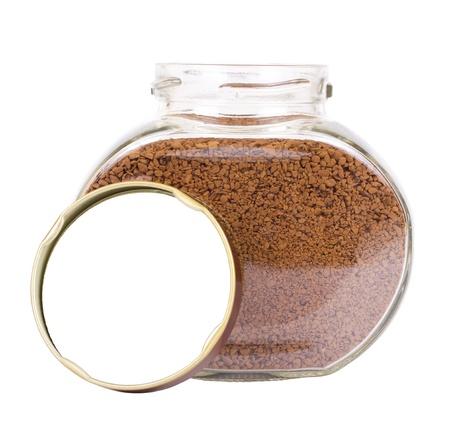 freeze dried: El frasco de vidrio transparente con una cubierta marr�n cerca de �l y cubiertos con un caf� liofilizado aislado