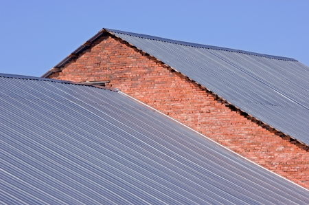Corrugated metallic gray roof on red brick building photo