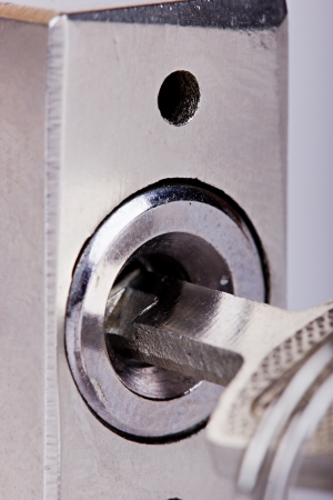 unauthorized: The macro metal padlocks hole with a key inserted Stock Photo