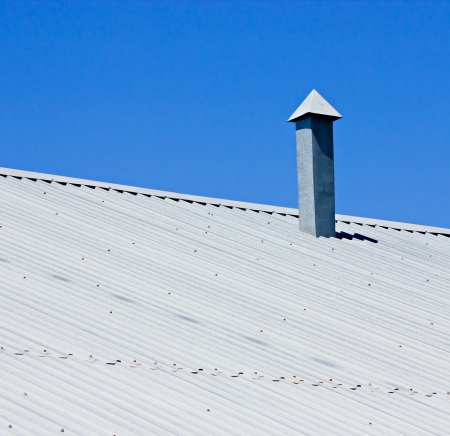 Corrugated metallic gray roof with ventilation pipe photo