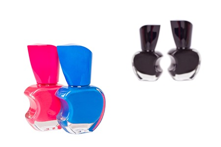 condemnation: Pink nail polish bottle and blue one standing together on foreground with focus on them and two black bottles on background isolated on white