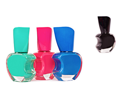 condemnation: Three nail polish bottles (green, pink and blue) standing together on foreground with focus on them and black bottle Stock Photo
