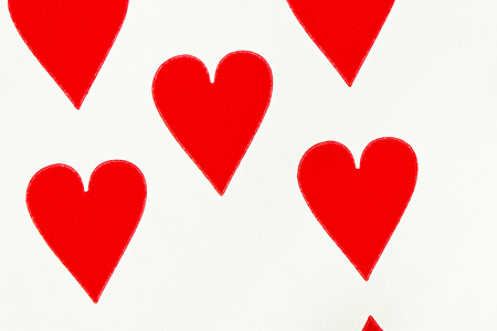 showed: Fragment of hearts suit playing card (three hearts wholly and two hearts partially showed)