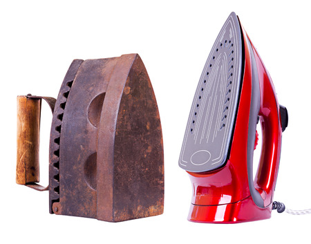Old vintage brown iron working on charcoal and new red one with grey bottom standing vertically isolated on white photo