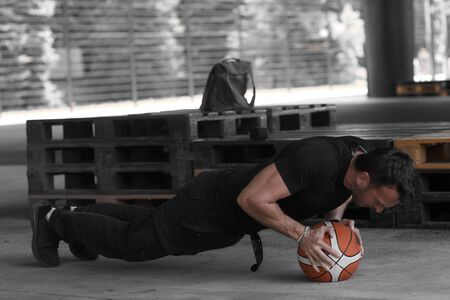 A man is pushing up on a basketball ball in a black tank top and black sweatpants