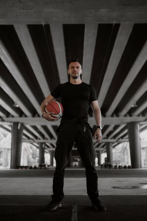 A man stands with a basketball ball dressed in a black T-shirt and black sweatpants 版權商用圖片