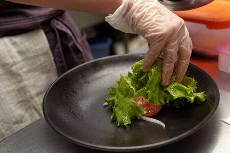 Chefs hands spreads food on a blue plate close-up