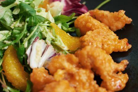 Shrimp in batter close-up on a black plate