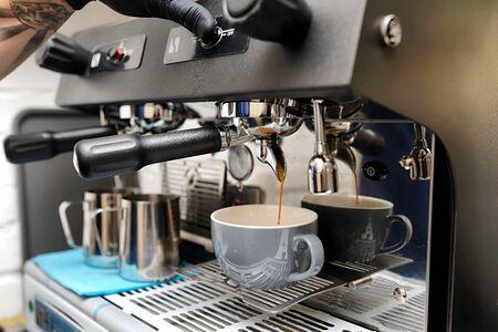 Nahaufnahme des Espressos gießend aus Kaffeemaschine. Professionelle Kaffeezubereitung