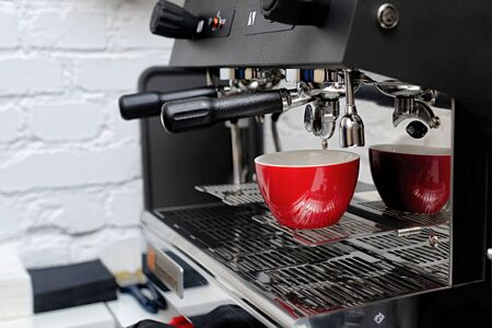 coffee machine preparing fresh coffee and pouring into red cups at restaurant