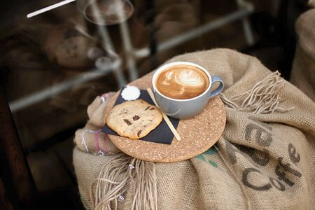 Coffee with froth and coffee beans in a sack on bag