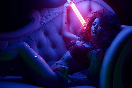 sexually beautiful fitness model is lying on the sofa with neon lights in lingerie, blue and red color, portrait of a girl